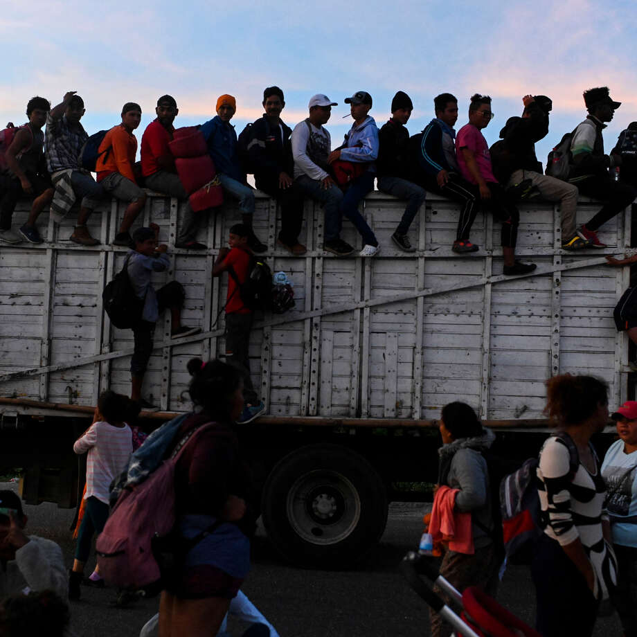 Some of the thousands of migrants traveling in a caravan toward the U.S. border ride atop trucks along a highway in Santiago Niltepec, Mexico, on their way to Juchitan, Mexico, on Oct. 30, 2018. Photo: Washington Post Photo By Carolyn Van Houten. / The Washington Post