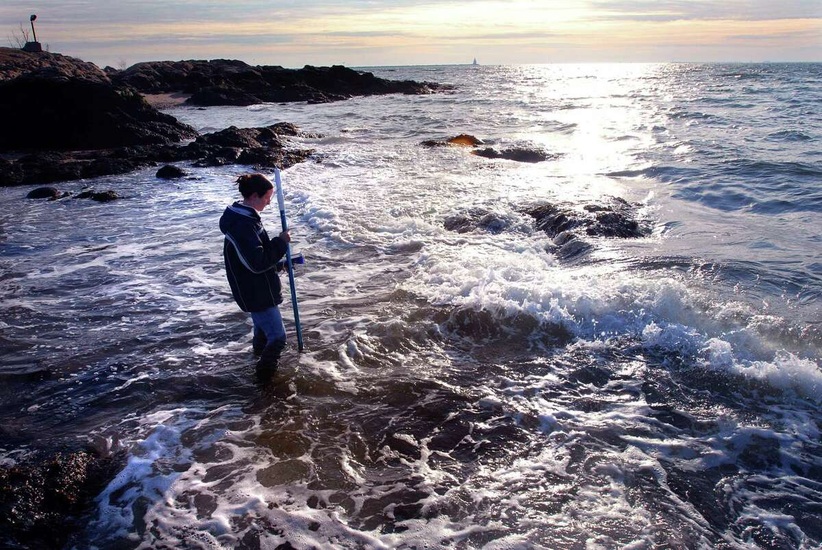 A student measures wave velocity along the shoreline at Lighthouse Point Park.