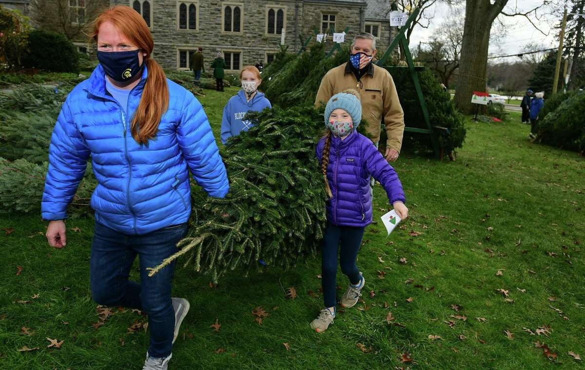 Local residents including Erin Wilson and her husband John and their daughters Macky and Morgan, 10 and 9, shop at The First Congregational Church of Greenwich Annual Tree & Wreath Sale Saturday, November 28, 2020, in Greenwich, Conn. The sale runs weekends beginning Saturday through Sunday, December 6 while supplies last. The sale features 500 fresh cut Fraser and Balsam fir trees from New Hampshire and more than 200 balsam wreaths and roping. All proceeds will benefit local charities including Kids in Crisis, Children's Learning Center, Inspirica, Mothers for Others, Pacific House (young adult program), and First Church Fund to Benefit New Covenant Center Soup Kitchen.