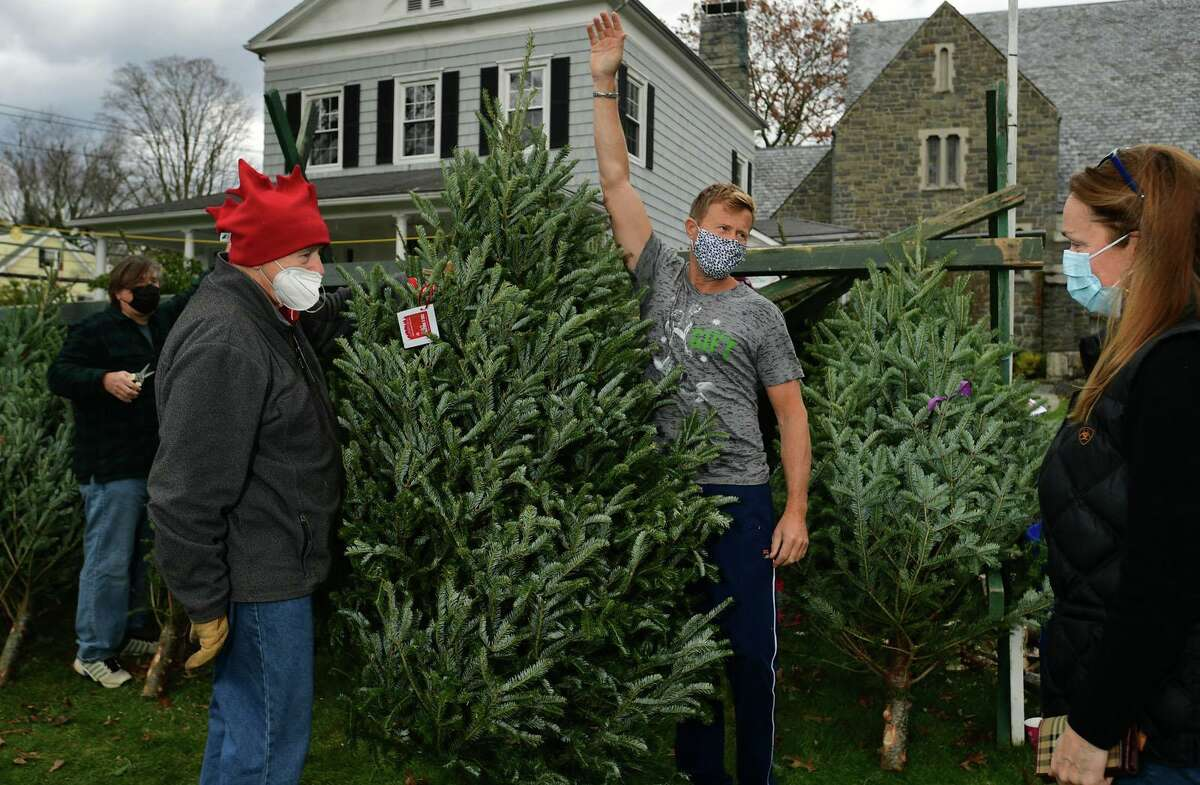 Volunteer Don Breismeisler helps local residents including Gary and Lorie Cunningham shop at The First Congregational Church of Greenwich Annual Tree & Wreath Sale Saturday, November 28, 2020, in Greenwich, Conn. Fresh-cut fraser and balsam fir trees from New Hampshire and more than 200 balsam wreaths and roping are for sale. All proceeds of the annual sale will benefit a number of local charities, including Kids in Crisis, Children's Learning Center, Inspirica, Mothers for Others, the young adult program at Pacific House, and the First Church Fund to benefit the New Covenant Center Soup Kitchen. For more information, visit www.fccog.org/ or call 203-637-1791.