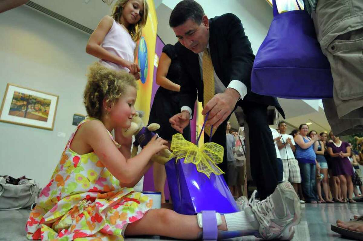 Hannah Sames accepts a bag of gifts from UAlbany President George M. Philip. (Philip Kamrass / Times Union )