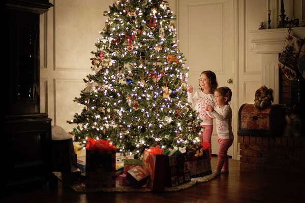 Young girls decorating Christmas tree at night in pajamas