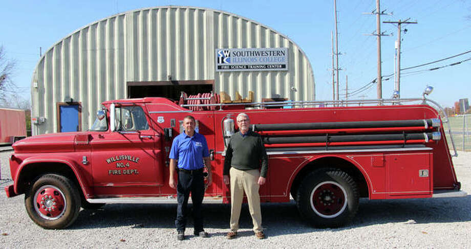 Retired Fairview Heights firefighter Daniel Lougeay of Marissa, right, and son, Southwestern Illinois College SWIC Fire Science Program Coordinator Curt Lougeay, stand with the donated the 1963 Fire Engine that Daniel donated to the SWIC Fire Science Program. Photo: Courtesy Of SWIC Photo By Jim Haverstick