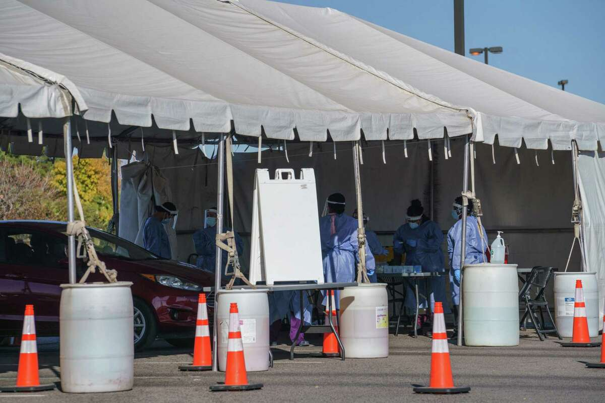 Healthcare workers administer tests at a drive-thru Covid-19 testing site in El Paso, Texas, U.S., on Monday, Nov. 30, 2020. El Paso Mayor Dee Margo said the recent spike in coronavirus cases can be pointed at