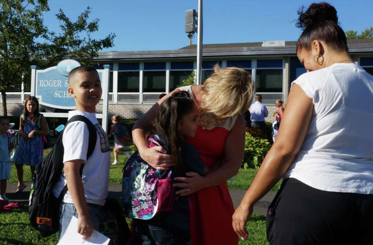 Returning Sherman School students get a hug from Principal Eileen Roxbee Thursday on the first day of school in 2014.