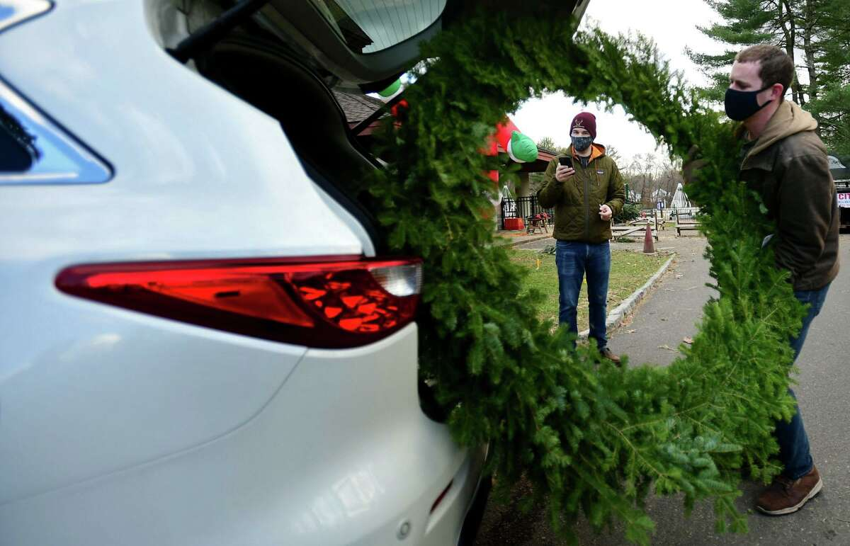 Tom Bach loads a giant wreath for New Canaan resident Jeff Biscoff during the Exchange Club Christmas tree sale Tuesday, December 1 at Kiwanis Park. More people are buying fresh trees and buying them earlier this year.