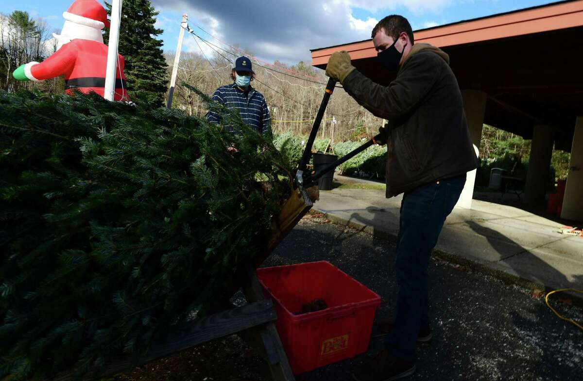 Tom Bach cuts a tree for a customer during the Exchange Club Christmas tree sale earlier in December 2020, at Kiwanis Park in New Canaan, Connecticut. More people bought fresh trees, and bought them earlier this year. The President-Elect, and President of the non-profit organization, and the Tree Lot Manager of the sale shows gratitude in this letter.