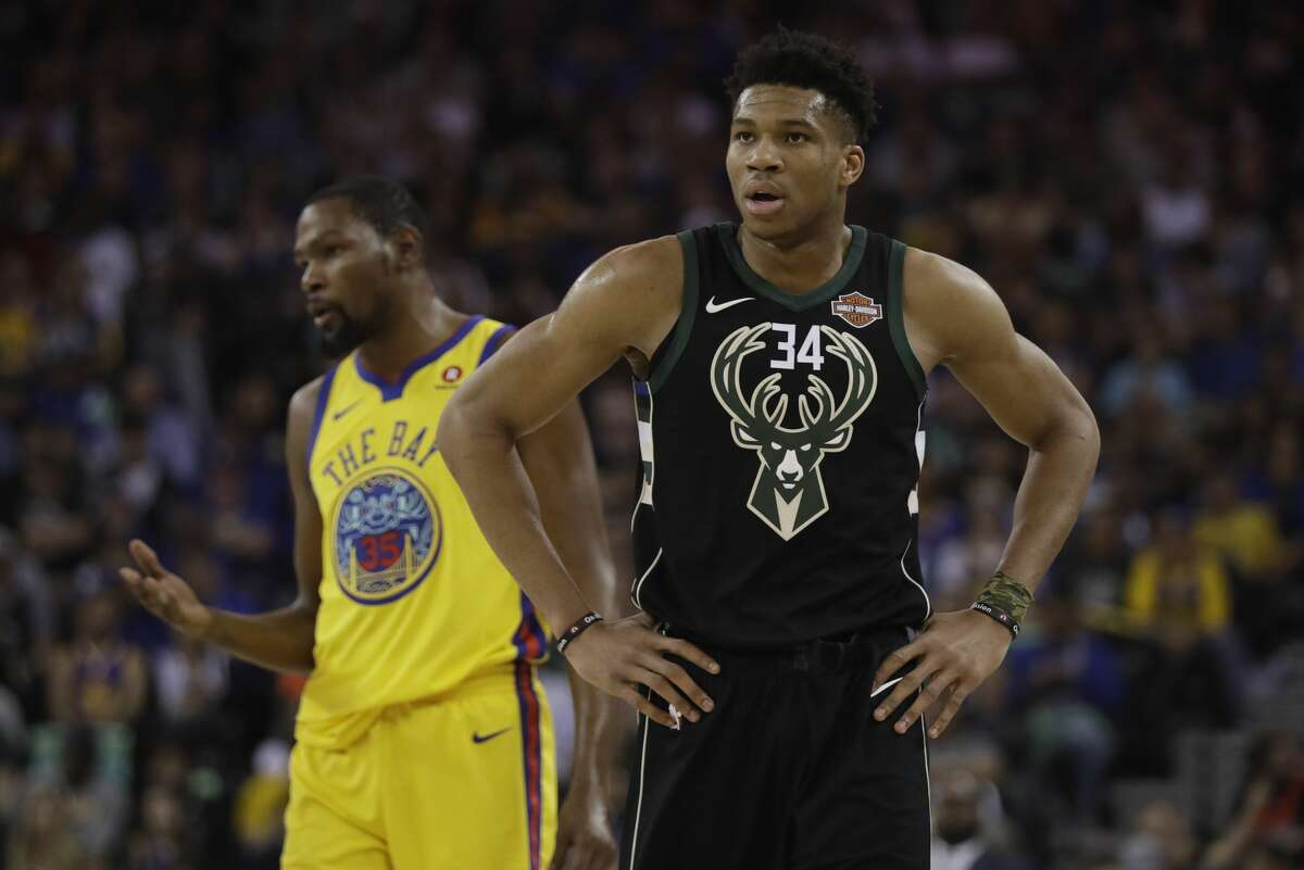 Milwaukee Bucks' Giannis Antetokounmpo stands in front of Golden State Warriors' Kevin Durant during the first half of an NBA basketball game Thursday, March 29, 2018.