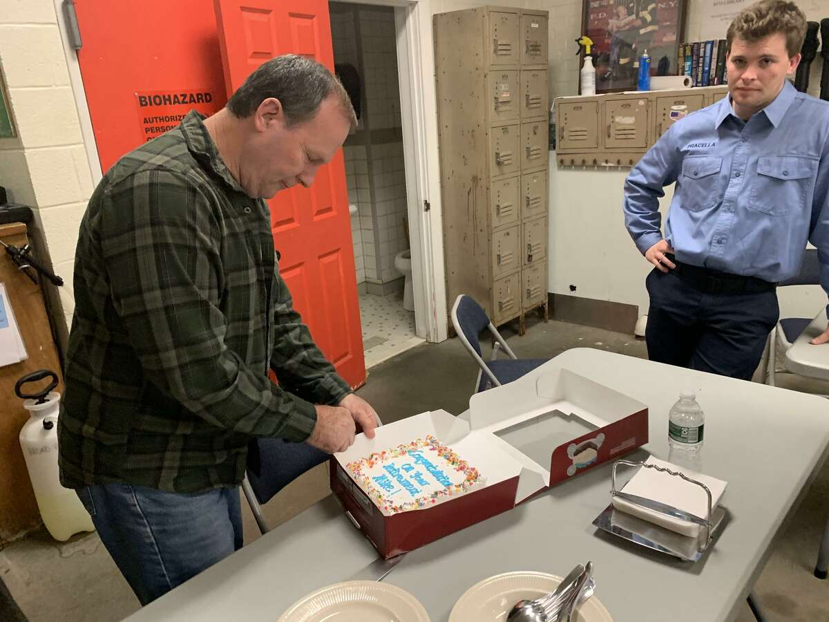 Mike Drake cuts the retirement cake on his last day on the job, the week before Thanksgiving. Looking on from right is rookie firefighter Jeff Pracella, who will replace him.