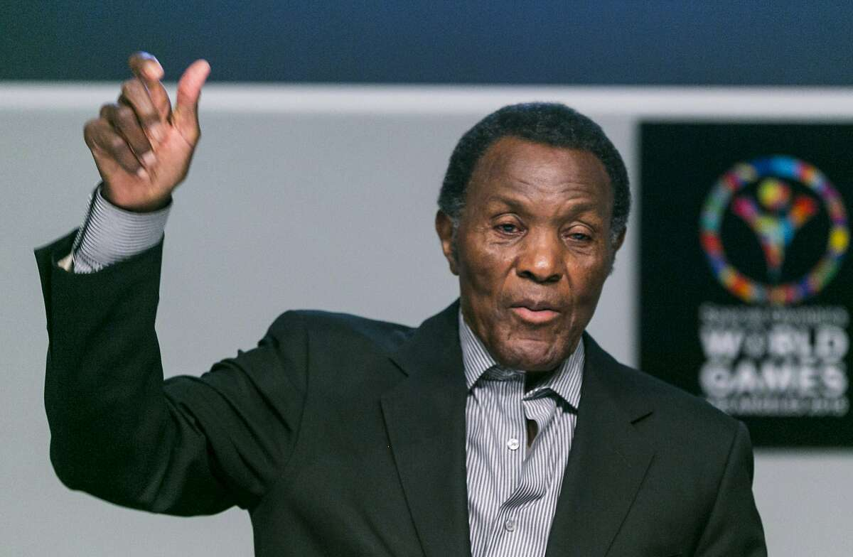 In this July 20, 2015, file photo, Olympic gold medalist and philanthropist Rafer Johnson lifts his arm to mimic the lighting of the Olympic torch as he recalls the first Special Olympics World Games he attended, during a news conference in Los Angeles. Rafer Johnson, who won the decathlon at the 1960 Rome Olympics and helped subdue Robert F. Kennedy's assassin in 1968, died Wednesday, Dec. 2, 2020. He was 86. He died at his home in the Sherman Oaks section of Los Angeles, according to family friend Michael Roth.