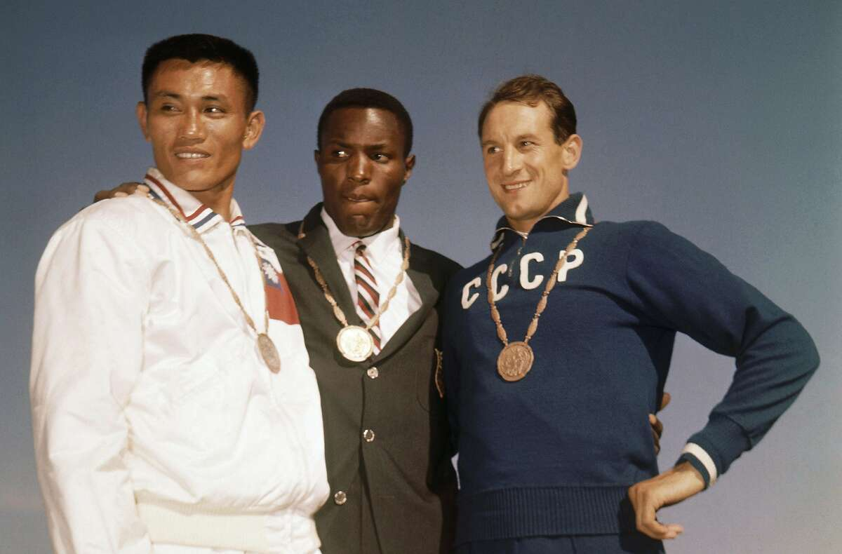 In this Sept. 6, 1960, file photo, the top three finishers in the decathlon of the 1960 Rome Summer Olympics stand on the podium while wearing their medals at Olympic Stadium in Rome. Rafer Johnson, center, won the gold; Taiwan's Yang Chuan, left, the silver; and Russia's Vasili Kuznetsov the bronze.