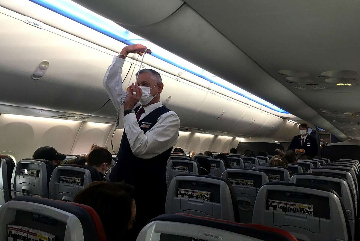 Flight attendants show safety precautions on an American Airlines Boeing 737 MAX airplane before it takes off on a test flight from Dallas-Fort Worth International Airport in Dallas, Texas, on Dec. 2, 2020.