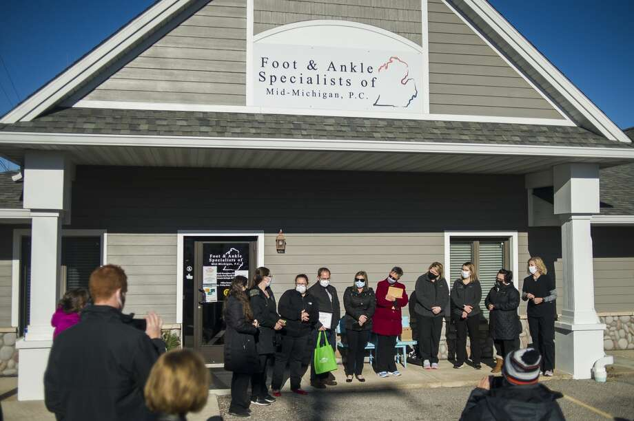 Community members and the Midland Business Alliance celebrate with the staff of Foot & Ankle Specialists of Mid-MI PC during a ribbon cutting ceremony Wednesday, Dec. 2, 2020 at the newly opened clinic at 111 E. Wackerly St. in Midland. (Katy Kildee/kkildee@mdn.net) Photo: (Katy Kildee/kkildee@mdn.net)