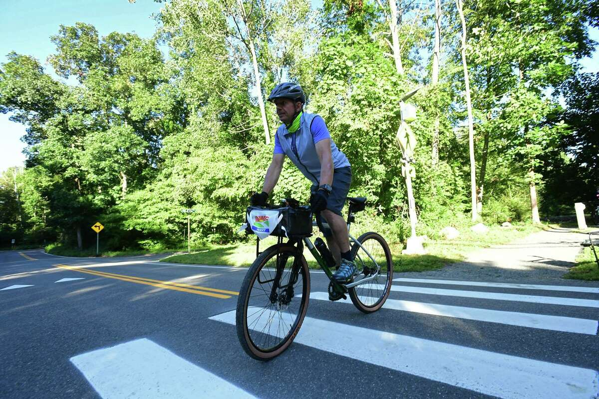 Mitch Ancona rides his bike 100 miles along a 2-mile loop of the Norwalk River Valley Trail to raise money for the trail on September 12, 2020, in Wilton.