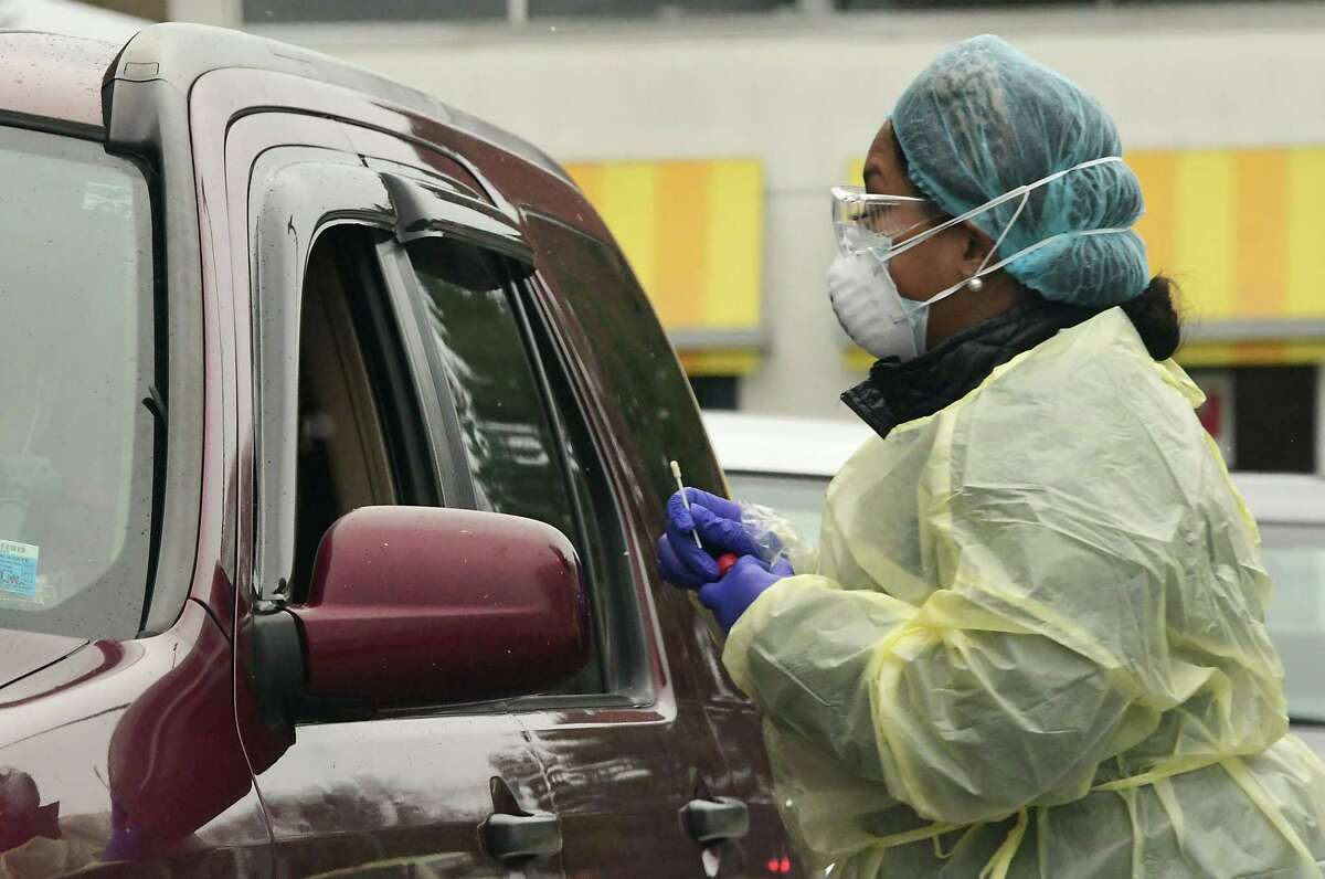 A healthcare worker attends to patients in a car at a walk-up and drive-through testing site at the Whitney M. Young Jr. Health Center Administrative Building on Wednesday, Dec. 2, 2020 in Watervliet, N.Y. Craig Gray of Albany fills out paperwork before his test at left. January 2021 was the deadliest month by far for Albany County residents, with 89 residents dying of COVID-19. (Lori Van Buren/Times Union)