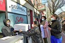 New Haven, Connecticut - Monday, November 24, 2020: Ivan Parra, a Sally's Apizza employee serves free takeout pizza to Yale New Haven Hospital employees nurse Alienne Salleroli, R.N. , Priscilla Steve (CQ), and nurse Curri Bower,R.N. as the famous New Haven Wooster Street pizzeria in New Haven is giving doctors, nurses and EMT personnel free small or medium pizza of their choice throughout day Tuesday as a show of appreciation and a tribute to the work they do.
