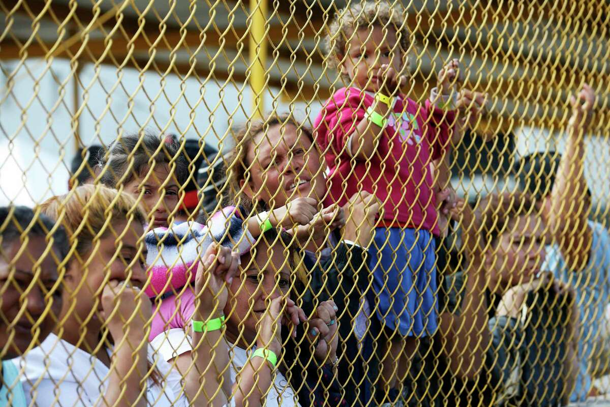 Central American immigrant families look out through the fence of a shelter in Piedras Negras, Mexico, toward Eagle Pass in 2019. The migrant crisis that had Donald Trump adopt wasn't of his making. President Barack Obama also struggled with a surge at the border.