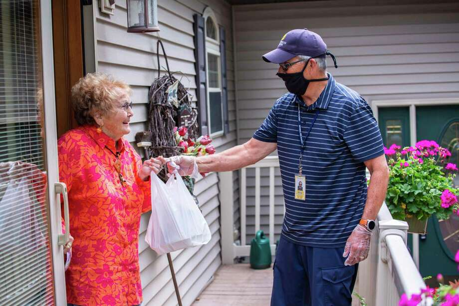 Ken Powell, a volunteer with Meals on Wheels, left, delivers a meal to Virginia Wackerle, right. (Photo provided/Senior Services of Midland County)