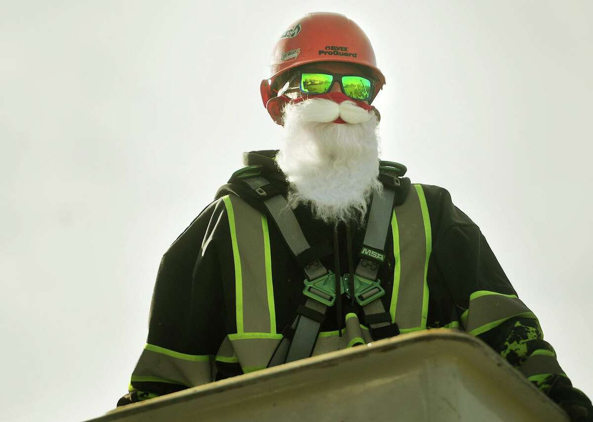 New Haven Parks employee C.J. Zemke dons a Santa Claus beard for the installation of a replacement Christmas tree for the one felled during a recent storm on the New Haven Green Wednesday, December 2, 2020.