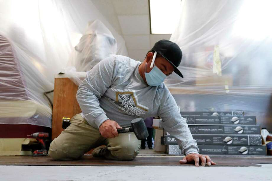 Carlos Rica, with Texas Engineering Roofing, helps install 440 square-feet of viynal flooring at The Candy House, Saturday, Nov. 28, 2020, in The Woodlands. A local company offered to install a new floor in the store for free as a community outreach project. The Candy House got a huge influx of business recently after a Facebook post went locally viral that incorrectly claimed the local business was in danger of closing. Photo: Jason Fochtman, Houston Chronicle / Staff Photographer / 2020 © Houston Chronicle