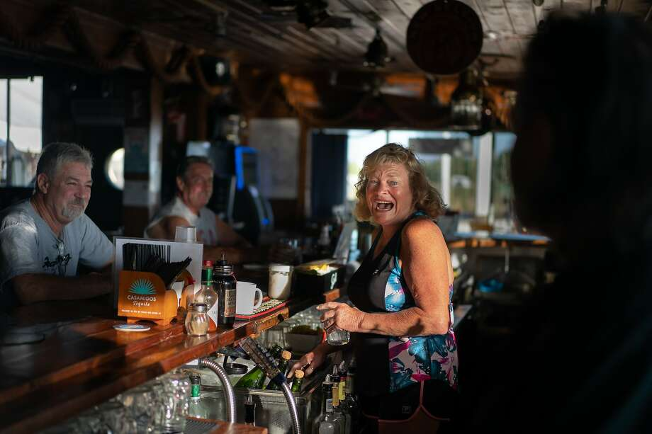 Long-time customer Marcy Hanley makes her own drink at the Rusty Porthole, a popular waterfront dining and drinking spot on Bethel Island. Photo: Paul Kuroda / Special To The Chronicle