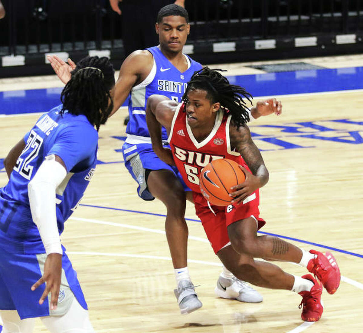 SIUE's Iziah James splits two SLU defenders off the drive during a Nov. 25 game in St. Louis. James and the Cougars were back in action Wednesday night at Northern Illinois in DeKalb.