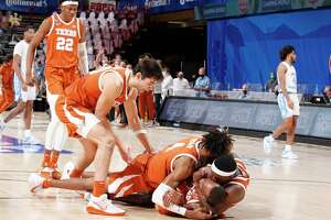 The Longhorns mob guard Matt Coleman after he made the game-winning shot to beat North Carolina in Asheville, N.C.