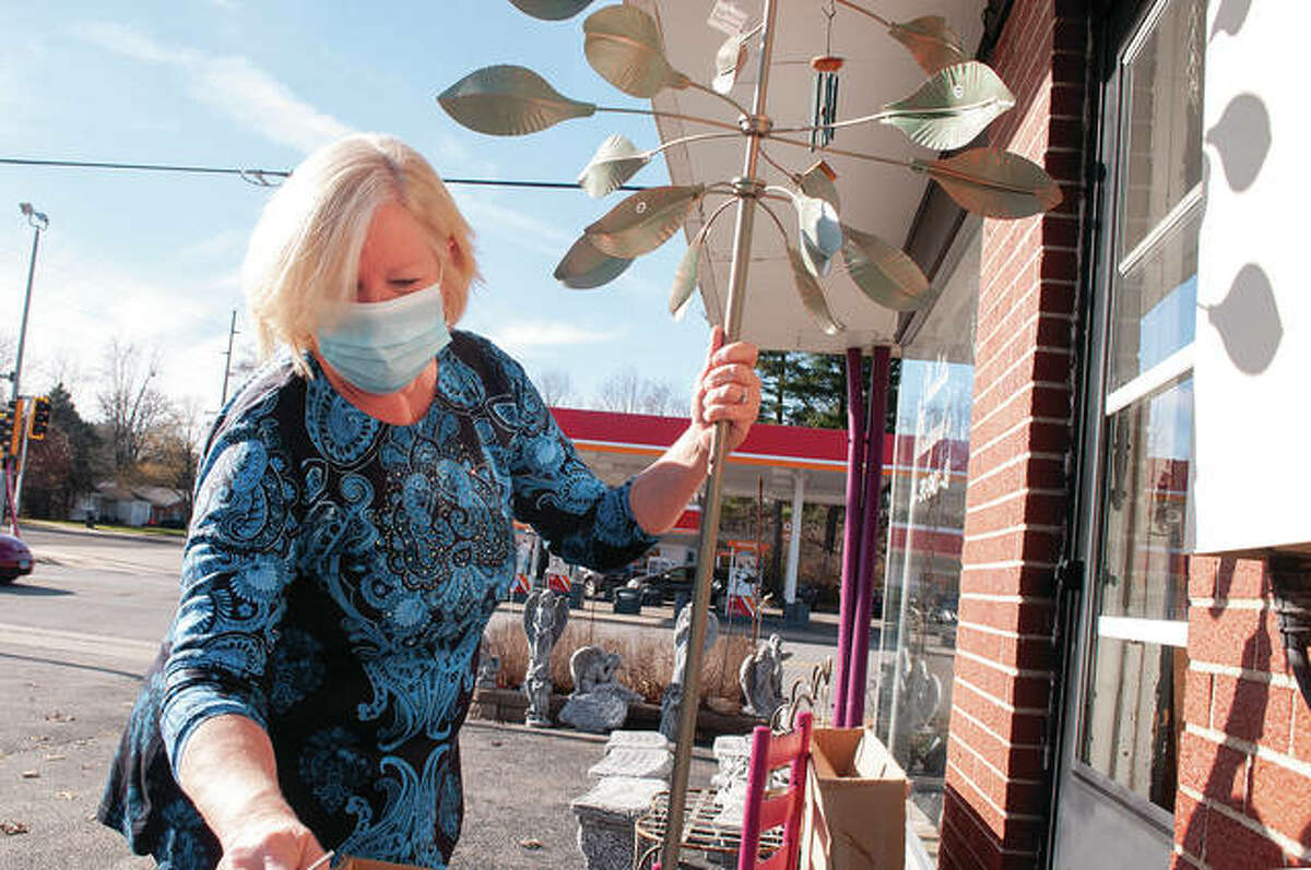 Charlotte Woodyard works Wednesday afternoon outside her store, Woodyard's, at 1724 S. Main St. Woodyard, who was putting together a wind spinner, said the spinners have been popular lately, with people having more time to work on projects around the home while waiting out the pandemic.