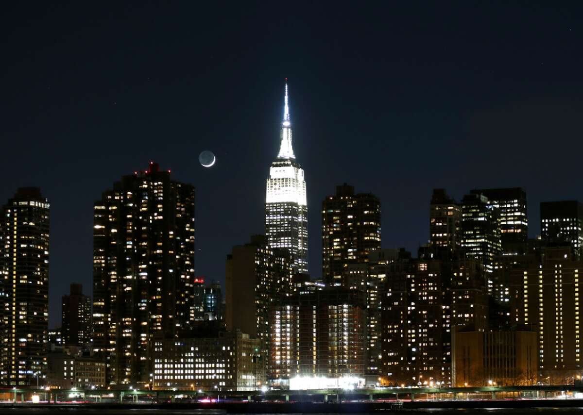 A crescent moon setting behind an eastside view of Manhattan and its illuminated Empire State Building in New York City.