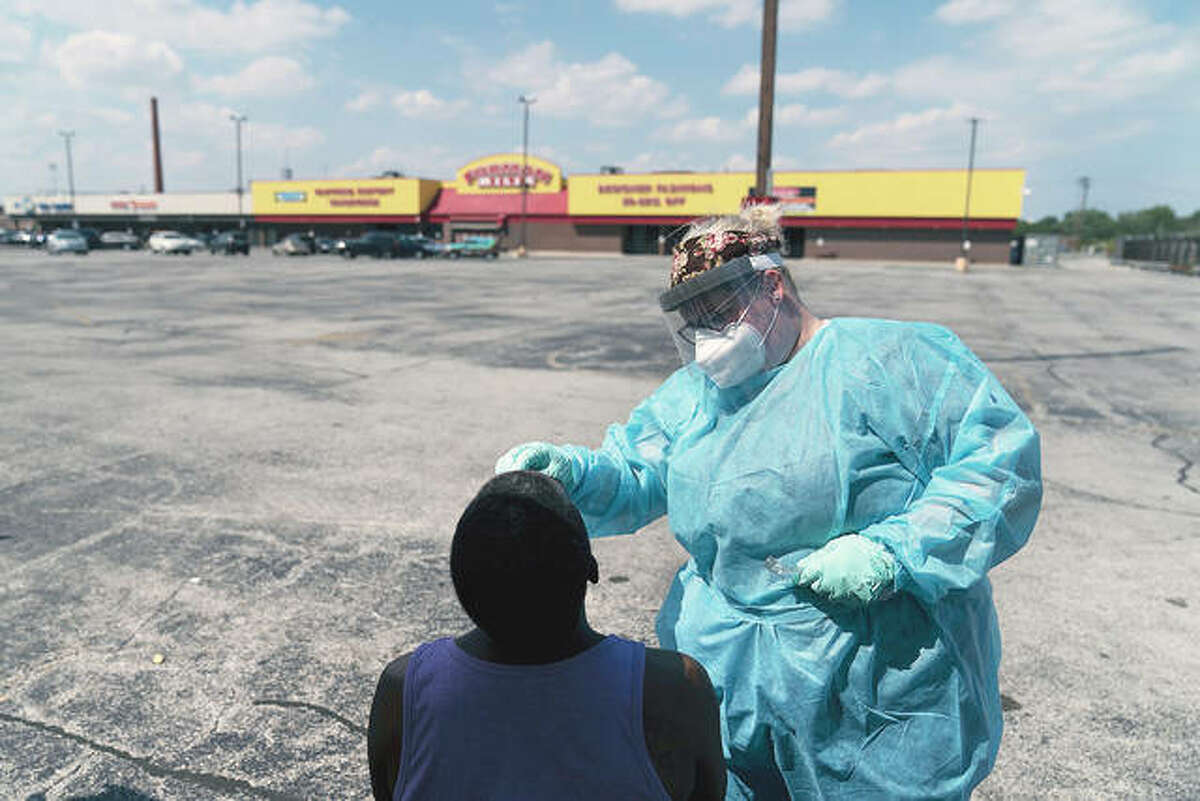 Phlebotomist Sarah Steffeter tests Phillip McTerron at a COVID-19 testing site in the parking lot of a shuttered store. Daily deaths related to the coronavirus pandemic in Illinois topped 200 for the first time Wednesday. The record 238 fatalities was nearly one-quarter higher than the previous high, set during the spring onslaught of the illness.