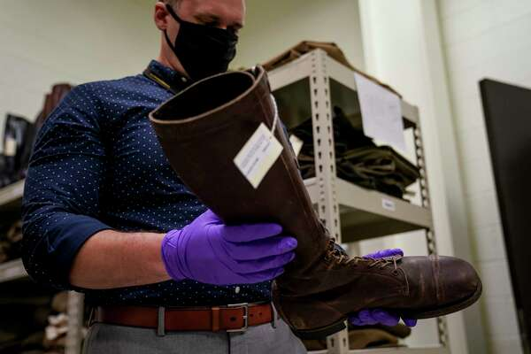 Paul M. Miller, chief curator of the Army Artifact Collection, holds a mid-20th-century cavalry boot that is among the items being divested from the Museum Support Center at Fort Belvoir, Va.