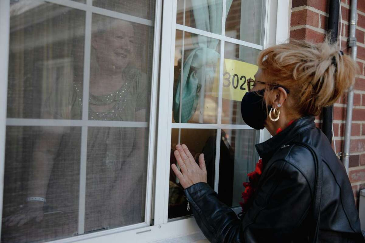 Kathy Moore, left, talks to her sister-in-law Ann Marie Lagrange, of Windsor Locks, through the window at Manchester Manor Health Care Center.