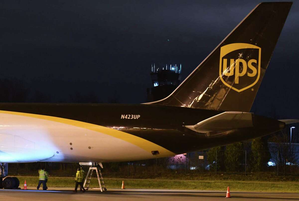 Workers inspect the fuselage of a United Parcel Service Boeing 757 cargo plane after landing at Albany International Airport on Wednesday night, Dec. 2, 2020, in Colonie, N.Y. UPS has increased its flights into the Capital Region to handle a surge in shipments. (Will Waldron/Times Union)