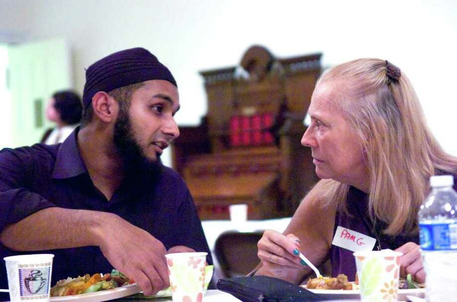 Faisal Quadri and Pam Groeschner chat as an interfaith community gathers at the First Congregational Church on Walton Place for Iftar, an evening meal when Muslims break the Ramadan fast, Thursday, September 2, 2010. The interfaith group joined the Muslims in fasting for the day and then gathered at sunset to break the fast by first eating a date and then praying before their meal. Photo: Keelin Daly / Stamford Advocate