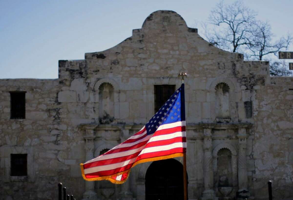 """The U.S. flag waves in front of the Alamo during a reenactment of the delivery of William B. Travis' """"Victory or Death"""" letter in San Antonio."""
