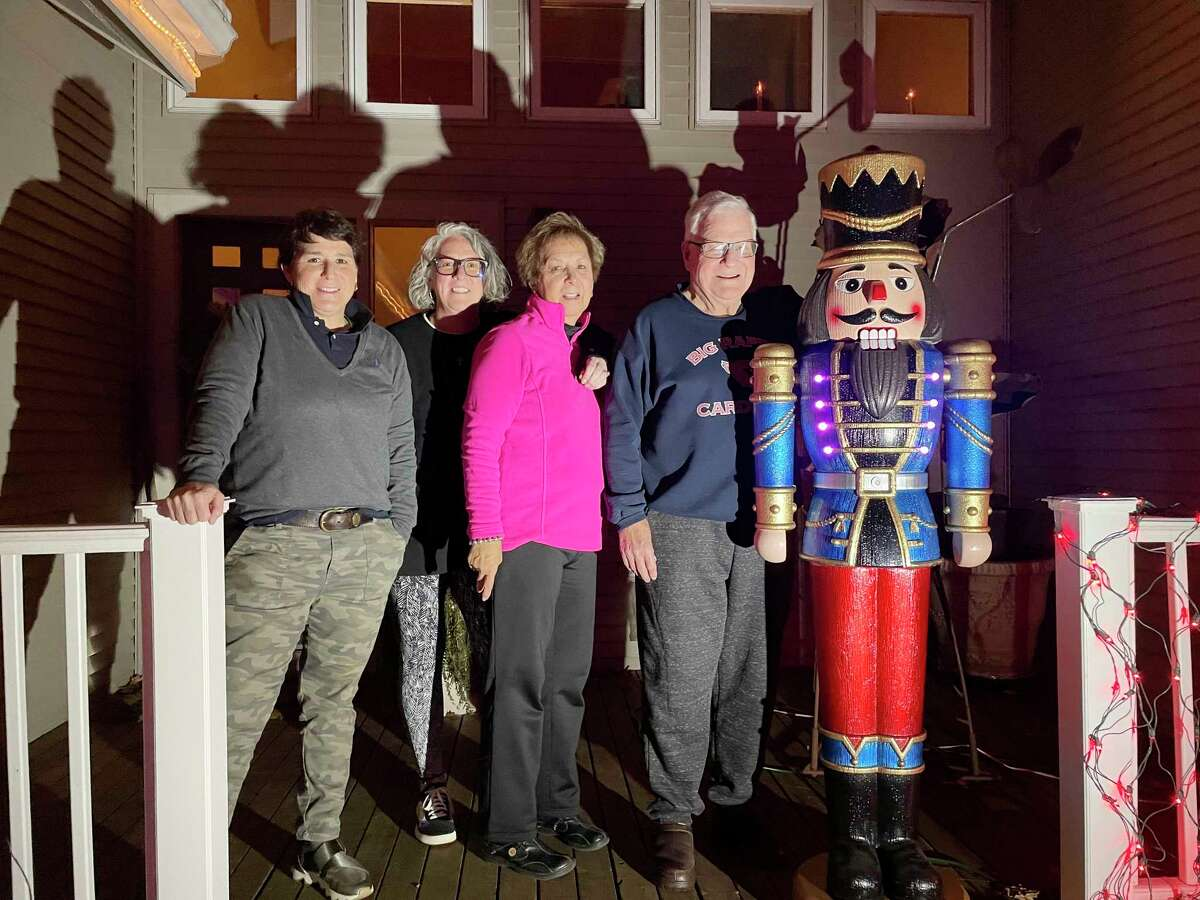 """(From left) Renee, Kristi, Lucy and Pete Kent stand outside their lit Big Rapids home to share a smile with the camera. For over 30 years, the Kent family has kept the Christmas spirit alive with a """"Wonderland of Lights"""" displayed throughout their yard on Golfview Drive. (Pioneer photo/Bradley Massman)"""