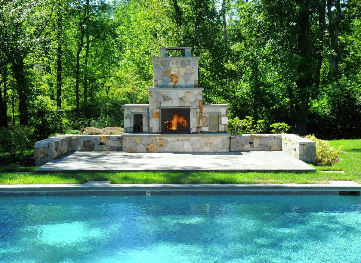 The outdoor fireplace at 12 Carrington Drive, Greenwich, sits poolside and among 4.01 acres. Houlihan Lawrence is the listing brokerage for the property; the current asking price is $2.495 million. Outdoor fireplaces come in an array of options - from wood-burning to gas, from masonry marvels of hand-formed fieldstone or stacked stone to pre-fabricated kits for at-home assembly. Unlike open wood-burning fire pits, an outdoor fireplace affords warmth, ambiance, and channeled smoke that goes up the chimney and away from those gathered 'round it. Houlihan Lawrence Realtor Ellen Mosher refers to the six-bedroom colonial at 12 Carrington Drive, Greenwich, as an