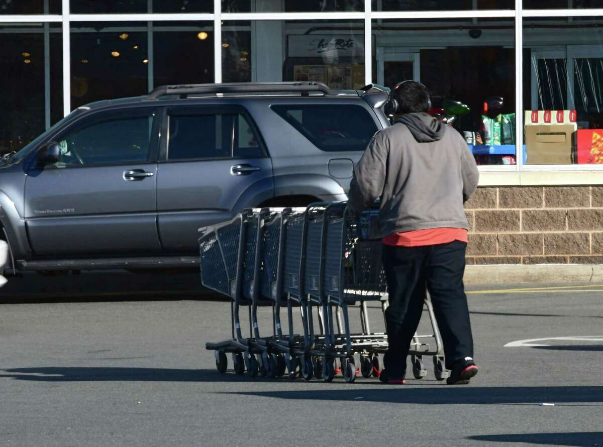A Shoprite employee rounds up the shopping carts and brings them in the store at Shoprite on Central Ave. on Thursday, Dec. 3, 2020 in Albany, N.Y. (Lori Van Buren/Times Union)
