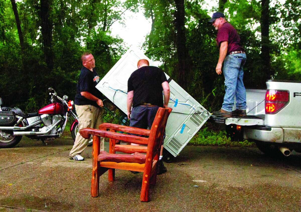 Mike Baudat, left, gets some help moving a refrigerator as he evacuates his home in River Plantation in Conroe on May 13, 2015.