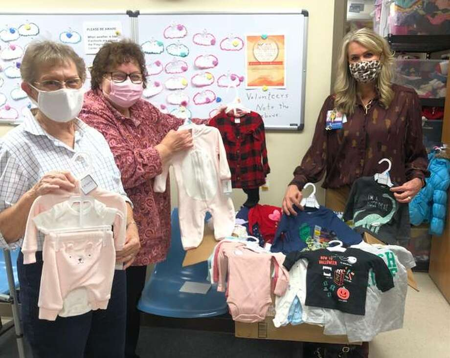 """Deb Meidel, nurse manager of HSHS St. Elizabeth's Women and Infants Center (right), presents gift cards and clothing recently collected at the hospital's """"Bundles for Babies"""" donation drive to Pregnancy Care Center volunteer, Gloria Schwartz, and director, Dr. Kay Bennett."""