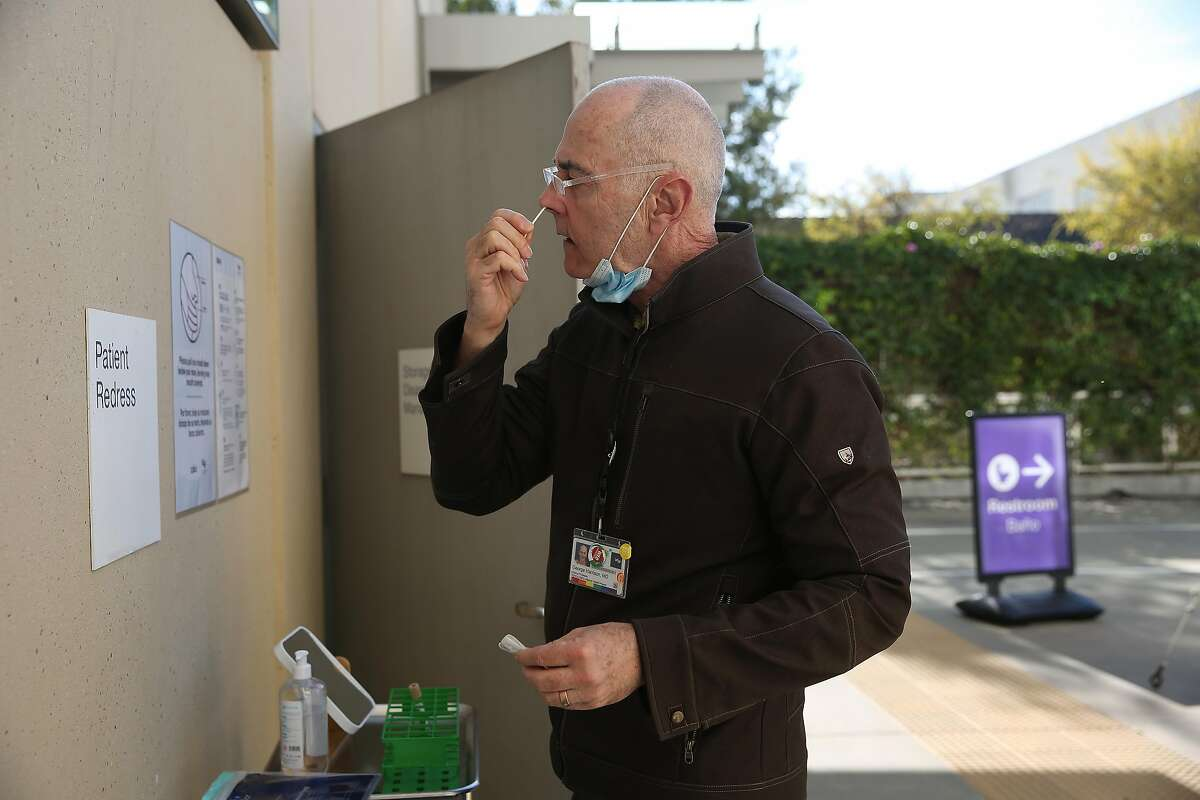 Dr. George Harrison uses a COVID-19 test kit at UCSF Mission Bay. Testing statewide is up at least 20% from a month ago.