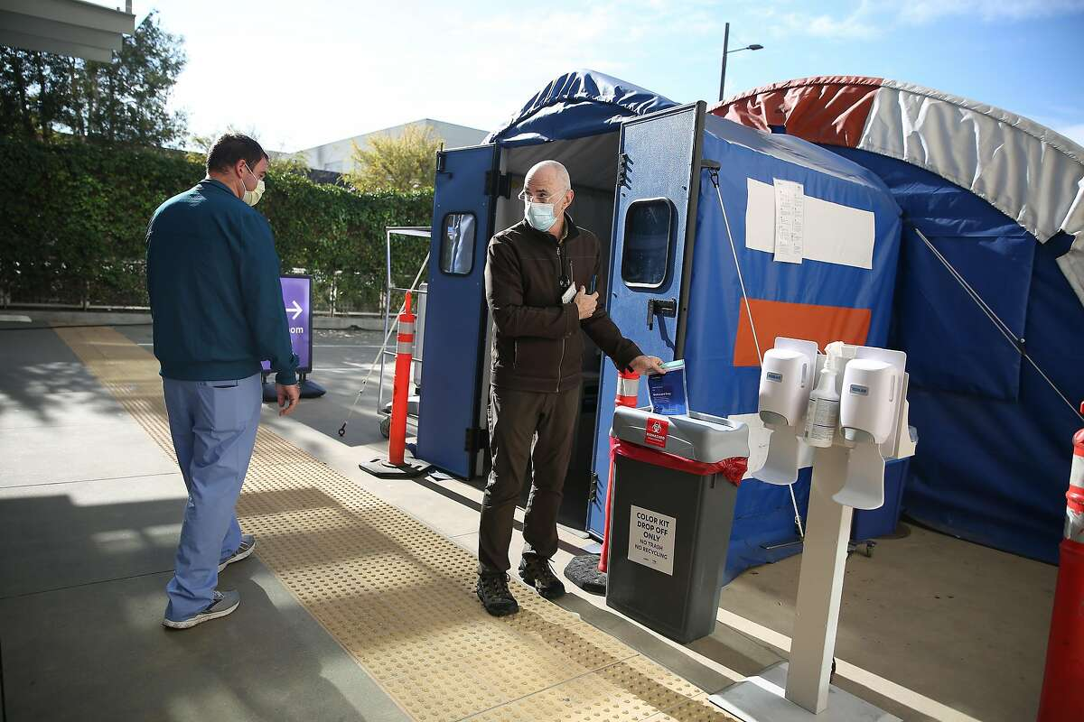Andrew Spinetti (left), patient care technician, assists Dr. George Harrison (right), UCSF physican, as he places the biohazard bag containing his nasal swab in collection tube into a drop off box at the self swab employee and student test drop-off site at UCSF Mission Bay on Wednesday, December 2, 2020 in San Francisco, Calif. UCSF and Color have collaborated to increase free COVID-19 testing for employees and students.