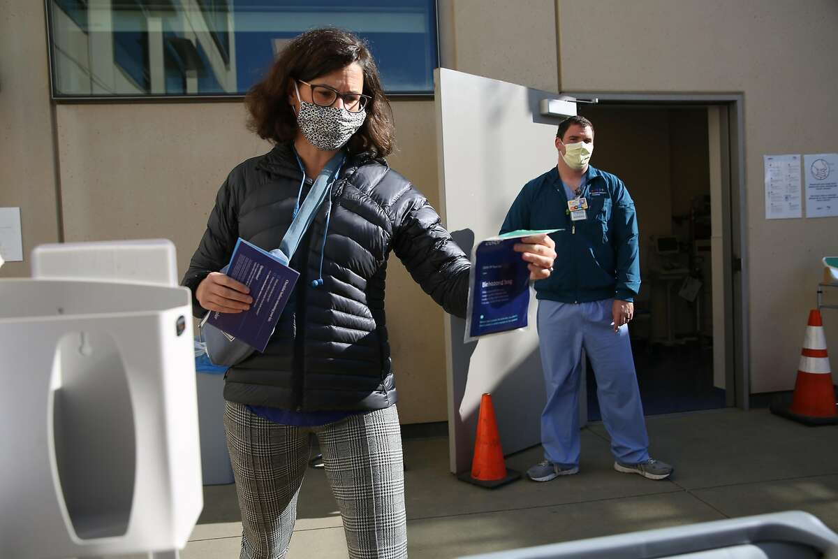 Andrew Spinetti (right), patient care technician, assists Dr. Jill Gleason, physical therapist (left), UCSF physican, as she places the biohazard bag containing her nasal swab in collection tube into a drop off box at the self swab employee and student test drop-off site at UCSF Mission Bay on Wednesday, December 2, 2020 in San Francisco, Calif. UCSF and Color have collaborated to increase free COVID-19 testing for employees and students.