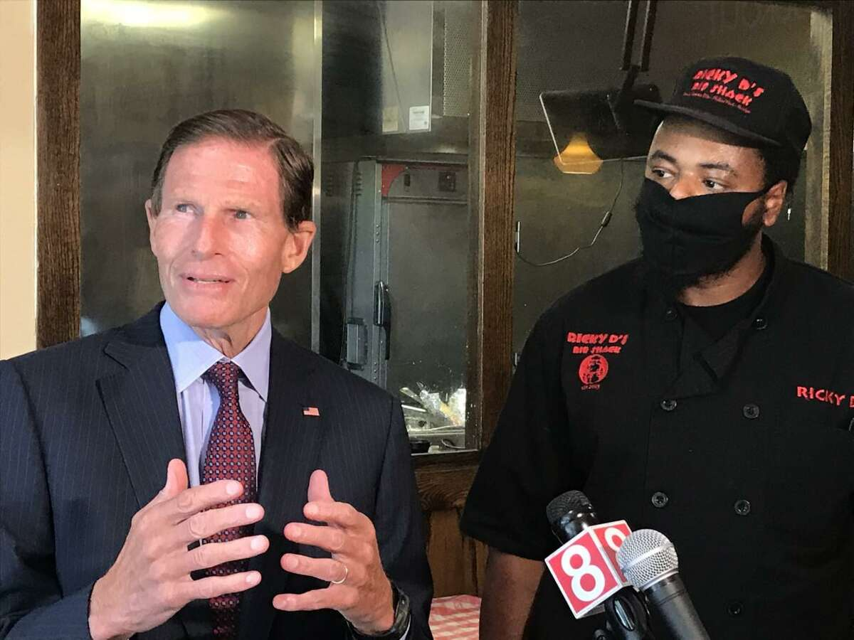 U.S. Senator Richard Blumenthal, D-Connecticut, and Ricky Evans, the owner of  Ricky D's Rib Shack in New Haven, talk with reporters Wednesday about the federal Payroll Protection Program. Blumenthal visited Evans' restaurant in an effort to urge that the $130 billion that remains in the program be focused on small and minority owned businesses.