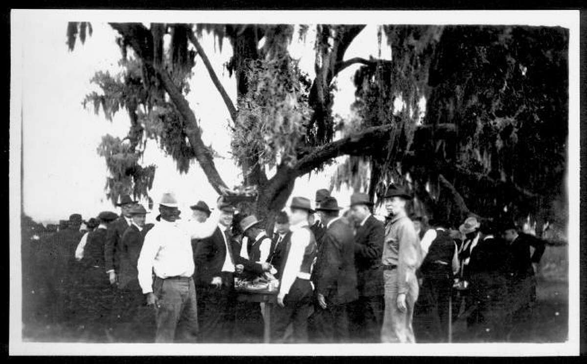 A large group of men standing near a table under moss draped oak trees at Camp George in 1920. African-American man in white shirt just to left of center is holding up a platter of barbecue to be served to the guests of the camp.