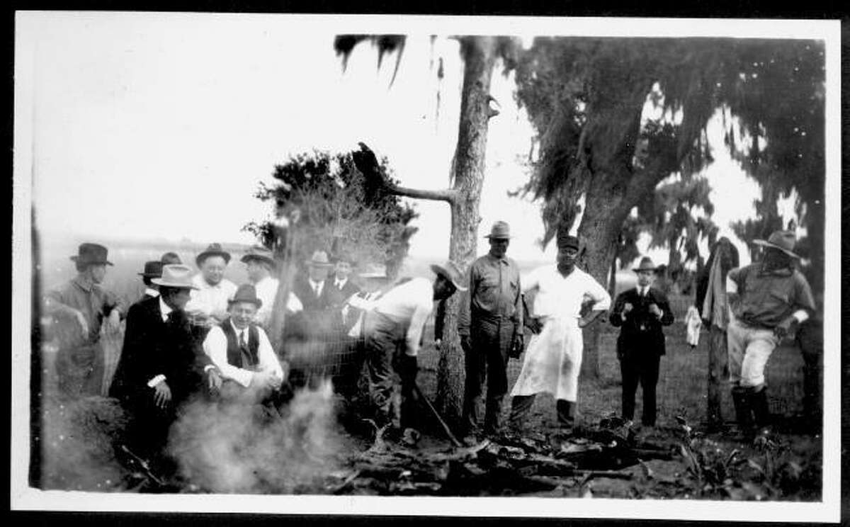 Photograph of a group of men near an underground barbecue pit at Camp George in 1920. The grill topped pit is filled with various meats.