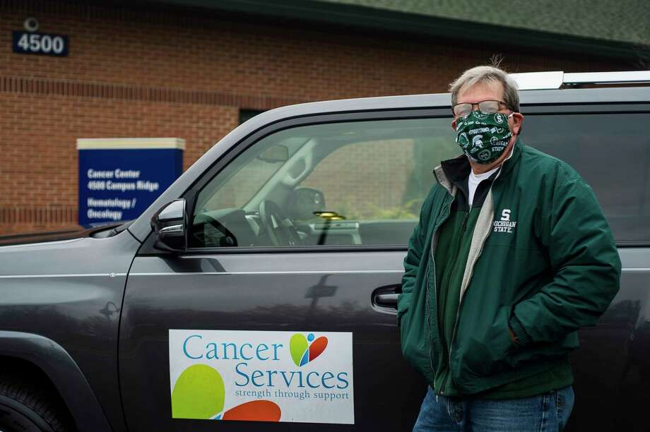 Mark Kuehl, a volunteer driver for Cancer Services of Midland, poses for a portrait Thursday in front of the MidMichigan Health Cancer Center in Midland. (Katy Kildee/kkildee@mdn.net)