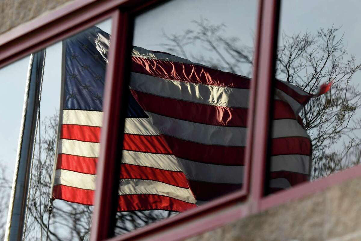 An U.S. flag is reflected on the exterior of Brunswick Fire Co. No. 1, Sycaway station, on Thursday, Dec. 3, 2020, in Brunswick, N.Y. The company is looking for ways to help retain and attract its volunteer firefighter membership. (Will Waldron/Times Union)