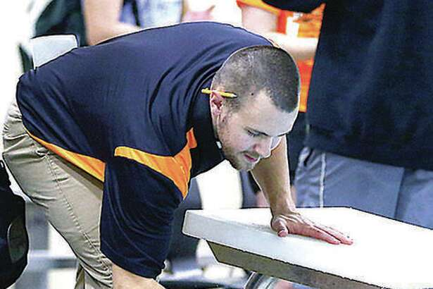 Edwardsville High swim coach Christian Rhoten congratulates one of his swimmers. Rhoten said that when it comes to guidelines from the IHSA, 'we have stopped having expectations or assumptions and just go by what it told us on any given day.'