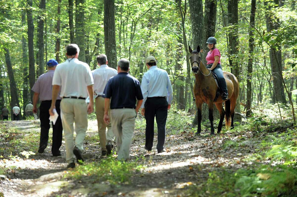 A horse and rider wait for a group from the state Siting Council, Ameresco and some town officials to pass during a walking tour of the area where there is a proposal to build solar panels on Candlewood Mountain in New Milford, Tuesday, Sept. 26, 2017.